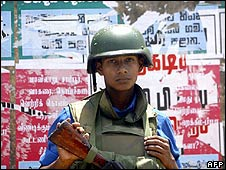 A Sri Lankan soldier stands by a wall covered in election posters in Trincomalee on 9 May