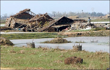 Villagers stand beside ruined houses in Twantay township on 9 May