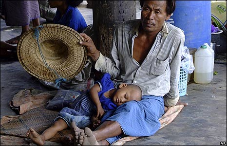 A cyclone survivor fans his son as they shelter at a monastery in Bogalay on 9 May