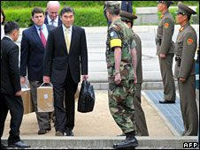 Sung Kim (C) carries a box as he crosses into South Korea, 10 May, 2008
