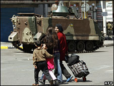 A Lebanese woman and her children walk past Lebanese soldiers in West Beirut, 10 may, 2008
