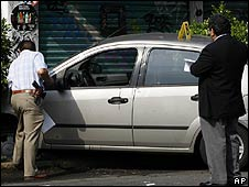 Police study the bullet-marked car of assassinated Mexico City anti-kidnap chief Esteban Robles on 9 May