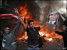 Sunni government supporters celebrate as they burn Baath Party offices in Tripoli on 10 May