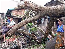 People sitting on a downed tree in Burma's capital, Rangoon