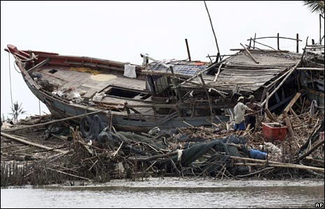 Villagers stand near a destroyed ship and repair their house in Pyapon, a town in the Irrawaddy Delta