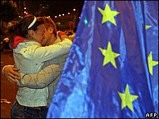 Tadic supporters embrace near an EU flag on election night in Belgrade
