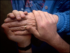 Pensioner and carer holding hands