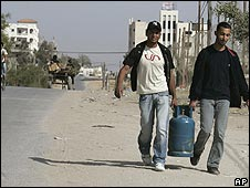 Gazans carry gas bottle