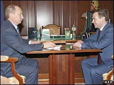 Russian Prime Minister Vladimir Putin (L) speaks with President Dmitry Medvedev (R)
