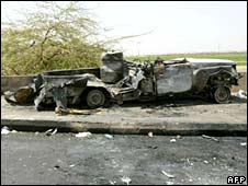 The remains of a burnt-out jeep sits on the pavement in Khartoum's twin city Omdurman