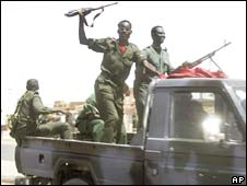 A member of the security forces in a passing vehicle raises his gun in the air in Khartoum's twin city of Omdurman