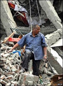 Man digging through rubble in Dujiangyan city