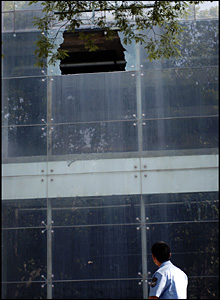 Policeman looks at a damaged building. Photo: Chris Cherry