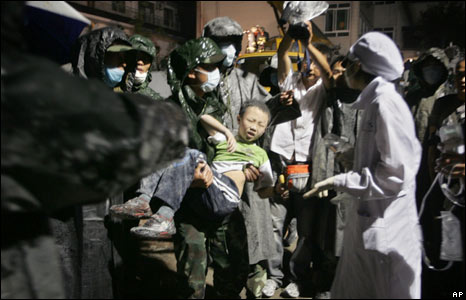 Rescue workers carry out a young boy from the rubble of a collapsed house in Dujiangyan