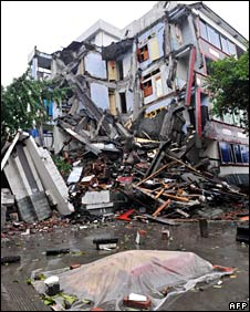A dead body covered with plastic lies in front of a collapsed building in Dujiangyan, Sichuan province