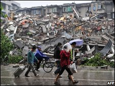 Residents walk past a collapsed building as they move out from Dujiangyan