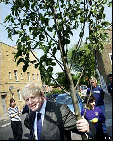 Mayor of London Boris Johnson grips a cherry tree which he helped plant during a planting initiative in Brixton