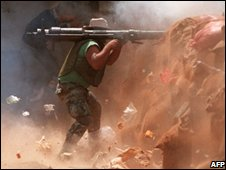An Amal militiaman armed with a B-10 soviet made rocket propelled grenade shots the Palestinian positions in Chatila , 1986