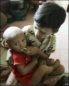 A boy feeds his younger brother at a temple being used as a temporary shelter on the outskirts of Rangoon (13.05.08)