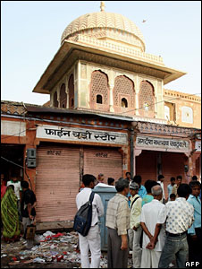 People stand at one of the sites of bomb blasts in Jaipur on May 14, 2008