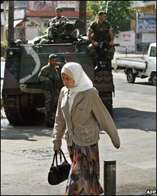 A woman walks past Lebanese soldiers in Beirut