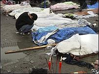Un hombre llora desconsolado ante varios cadáveres,  AP