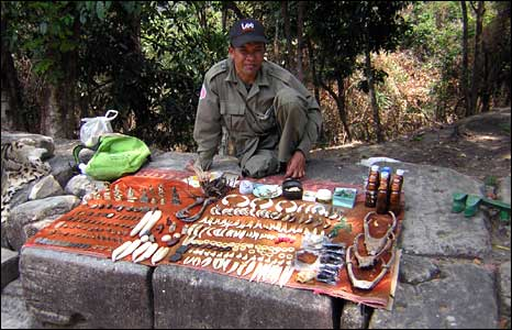 A Cambodian stallholder, selling trinkets and animal parts