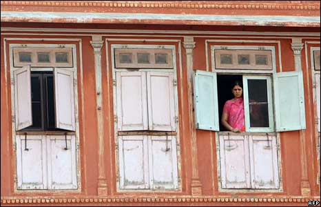 A woman watches from the window of her house the bomb blast site in Jaipur on May 14, 2008