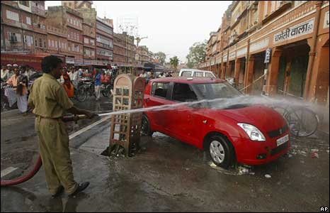 Fire force personnel spray water to clean up blood stains at a site where one of the bomb blasts took place in Jaipur, May 14, 2008
