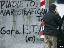 A man next to the scene of the car bomb, with writing on the wall reading 'Long Live ETA'