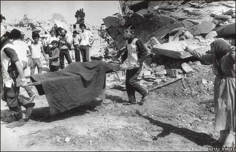 Workers remove the body of a Palestinian killed in Sabra and Shatila, 1982