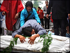 Woman grieving over coffin of her child