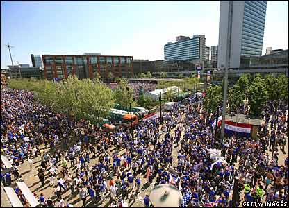 By lunchtime Rangers fans overtake Piccadilly Gardens with more arriving from Piccadilly Station (top left)