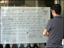 A man reads a poster drawn by the Fritzl family at the main square in Amstetten, Austria