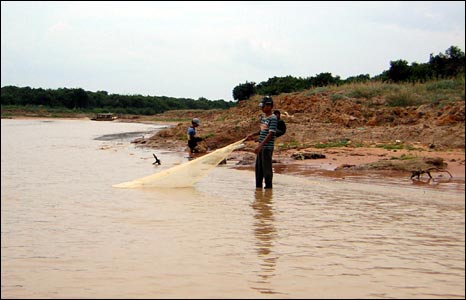A man fishes in a channel leading to the Tonle Sap lake