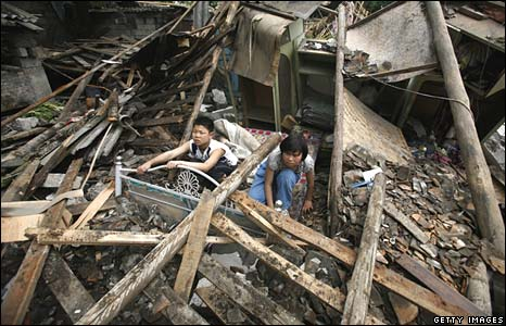 Chinese quake survivors attempt to salvage belongings inside their destroyed home on Thursday in Dujiangyan