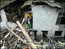 Victim looks out from his destroyed house