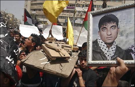 Palestinians with models of Israeli army vehicles and pictures of prisoners held in Israeli jails in a demonstration in Nablus, in the West Bank