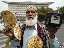 A man holds bread and an electric metre during a protest in Lahore. File photo