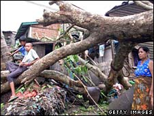 Family outside ruined home in Burma