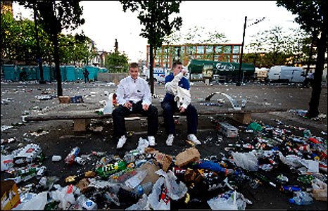 Two boys sitting on a bench surrounded by rubbish.