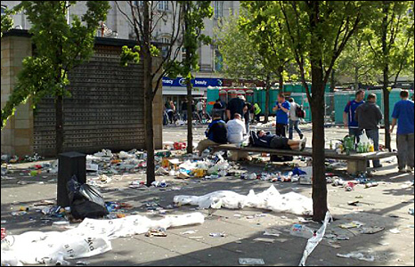 Rangers fans on a bench surrounded by rubbish.