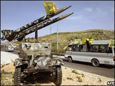 Hezbollah supporters pass a jeep laden with replica missiles on their way north to Beirut