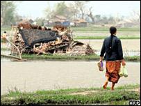 Una mujer pasa al lado de una casa destruida