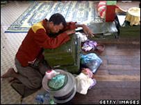 Un hombre descansa frente a un monasterio en las afueras de Rangún