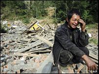 Un hombre llora en medio de los escombros en Sichuan, China.