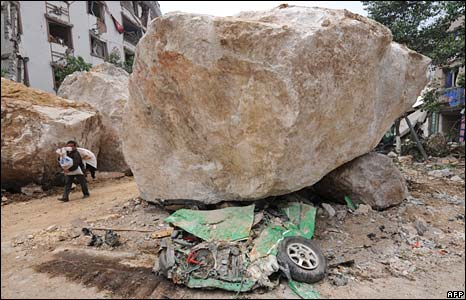 A flattened taxi lies under one of the boulders that crushed it on the earthquake damaged streets of Beichuan in Sichuan Province on May 16, 2008