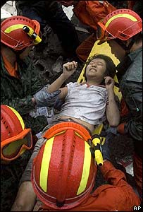A young girl is pulled free from the rubble
