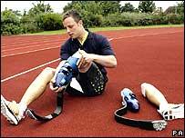 Pistorius ajustando una de sus prótesis sobre la pista