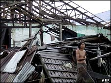A man stands among wreckage of a rice mill destroyed by the cyclone Nargis near Bogalay township